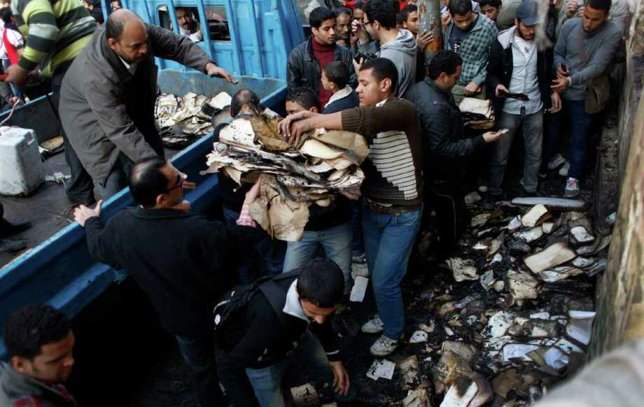 Egyptian protesters try to salvage valuable books and documents from the two story building of the Egyptian Scientific Complex, that is now in danger of collapsing after it was almost gutted by fire which broke out during clashes with army soldiers last Saturday, near Tahrir Square in Cairo, Egypt Monday, Dec. 19, 2011. Protesters blame troops for the fire that broke out in the historical complex that was set up during the three year occupation of Egypt by France in the late 18th century. (AP Photo/Nasser Nasser) Photo: Nasser Nasser / AP