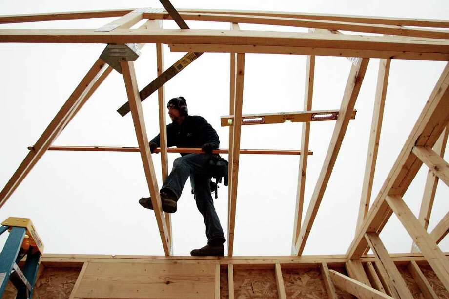 In this Nov.3, 2011 photo, Jim Weiler, of Jim Weiler Construction, sets a roof truss on a home under construction in LaPorte, Ind. Rising interest from would-be buyers is leaving U.S. homebuilders less pessimistic about the housing market. But tighter lending standards are still keeping many potential buyers from purchasing new homes. (AP Photo/Michigan City News Dispatch, Bob Wellinski) Photo: Bob Wellinski