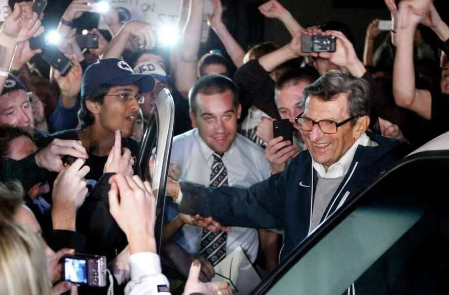 FILE - In this Nov. 8, 2011 file photo, students greet Penn State coach Joe Paterno as he arrives at his home in State College, Pa. The ouster of one of America's most revered coaches, Penn State's Joe Paterno, after shocking child sex abuse charges against his former assistant was overwhelmingly voted the sports story of the year by members of The Associated Press. Photo: AP