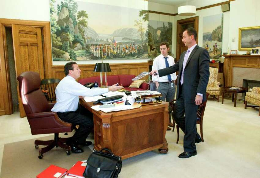 Roy Occhiogrosso shows Dan Malloy a copy of Connecticut Town & City Magazine that features the governor on the cover as the governor's scheduler Zack Hyde looks on.