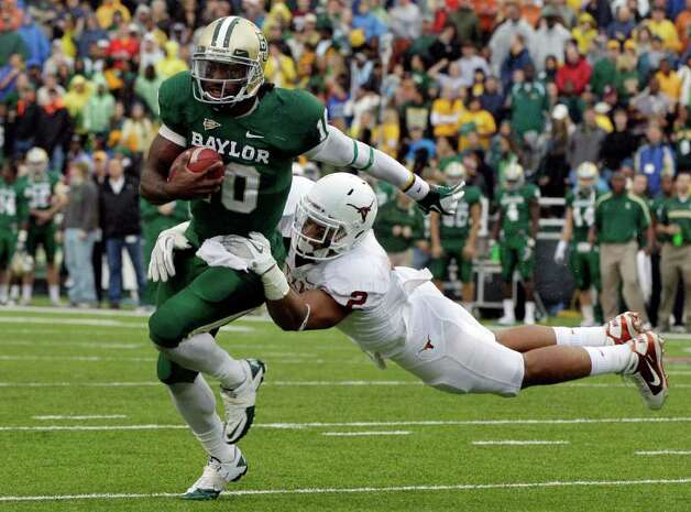 Baylor quarterback Robert Griffin III (10) attempts to escape a tackle by Texas cornerback A.J. White (2) in the first half of an NCAA college football game Saturday, Dec. 3, 2011, in Waco, Texas. Photo: AP