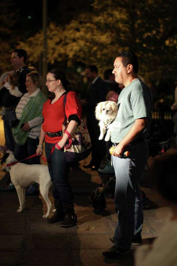 Attendees and their dogs attend a rally at Alamo Plaza to support the city's live release initiative and promote responsible pet ownership, Monday, December 19, 2011. Organizers and participants brought their pets and a flashlight to shine in the sky for pets in need. Photo: JENNIFER WHITNEY