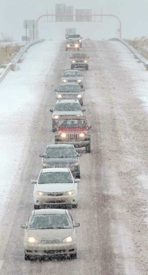 DEAN HANSON : ALBUQUERQUE JOURNAL SLOW, STEADY: Northbound traffic on I-25 approaches Santa Fe, N.M. in a single file as snow accumulates on the road, Monday as a winter storm hit the area. Photo: Dean Hanson / Albuquerque Journal