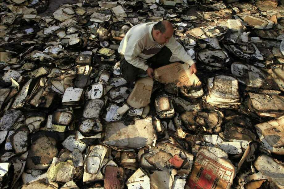 MOHAMMED ABED : AFP/GETTY IMAGES  CHARRED TREASURES: An Egyptian book restorer tries to salvage books at the Institute of Egypt in Cairo on Monday after the building caught fire during deadly clashes between security forces and protesters. The institute was founded in 1798. Photo: MOHAMMED ABED / AFP