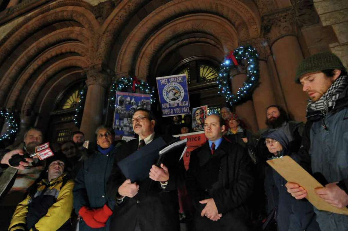 Albany Common Council Members Barbara Smith, Dominick Calsolaro, center, holding resolution, and Anton Konev talk about their resolution in support of campaign finance reform while standing on the steps of City Hall with some of the Occupy members, including Matthew Edge, far right, on Monday evening Dec. 19, 2011, in Albany, N.Y.. (Philip Kamrass / Times Union )
