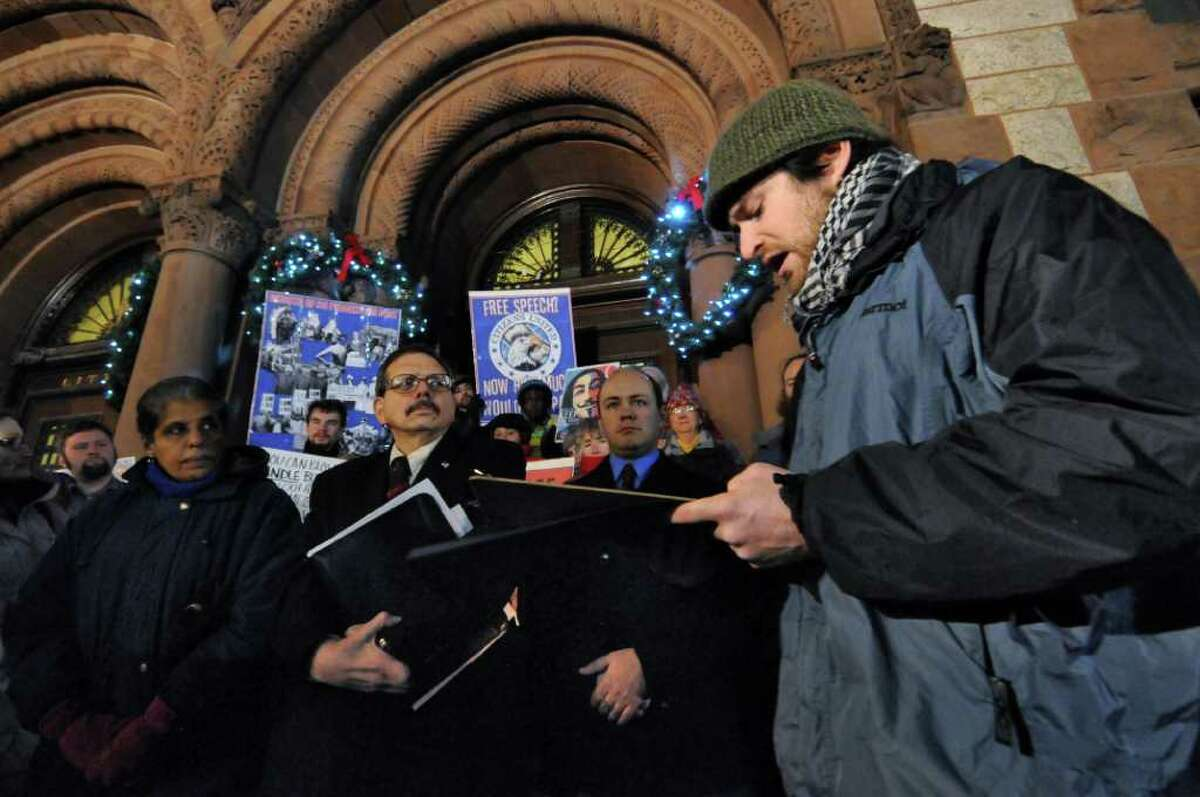 Albany Common Council Members Barbara Smith, Dominick Calsolaro, center, and Anton Konev listen to Occupy Albany member Matthew Edge, right, talk about the counci's resolution in support of campaign finance reform while standing on the steps of City Hall on Monday evening Dec. 19, 2011, in Albany, N.Y.. (Philip Kamrass / Times Union )