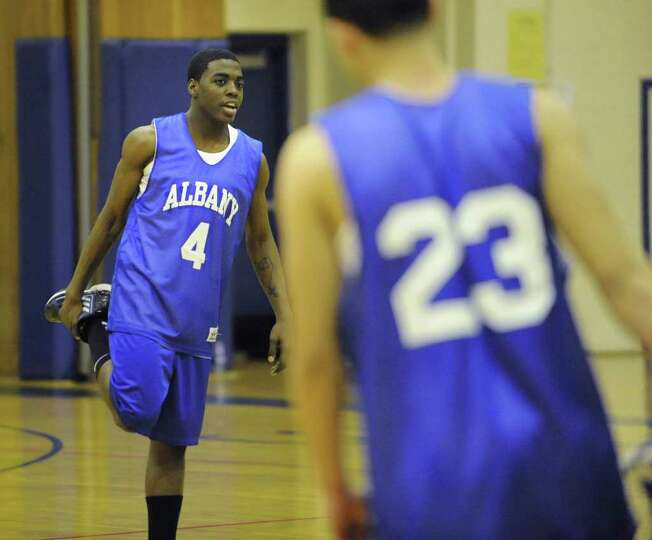 Albany High School basketball player Daquan Johnson leads the warm up exercises before practice with