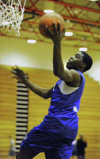 Albany High School basketball player Daquan Johnson goes for a layupl during practice with the team