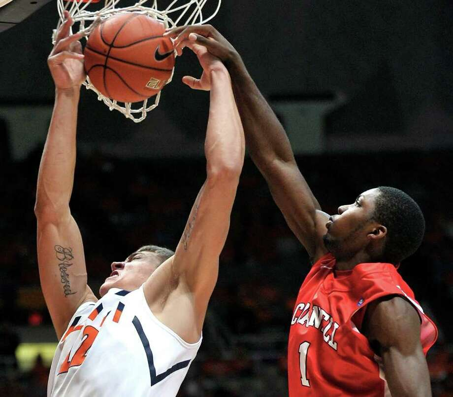 Illinois center Meyers Leonard (12) is fouled by Cornell guard Galal Cancer (1) in the first half of an NCAA college basketball game in Champaign, Ill., on Monday, Dec. 19, 2011. (AP Photo/Robin Scholz) Photo: Robin Scholz