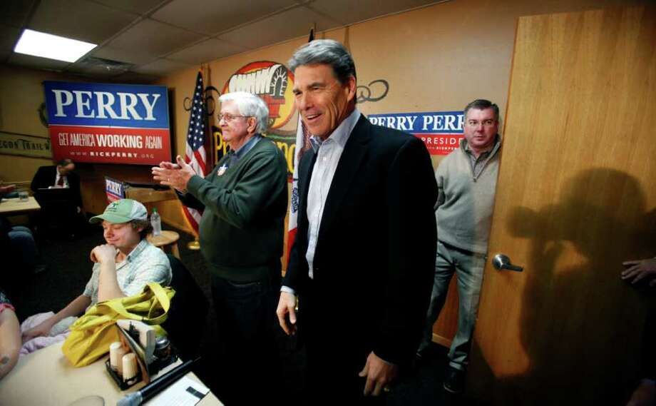 Republican presidential hopeful, Texas Gov. Rick Perry, center, reacts as he is introduced to speak to local residents during a campaign stop at the Pizza Ranch restaurant, Monday, Dec. 19, 2011, in Manchester, Iowa. (AP Photo/Charlie Neibergall) Photo: Charlie Neibergall