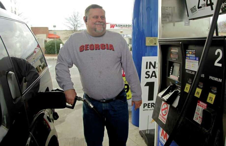 In this Dec. 15, 2011 photo, Michael Reed fills his gas tank at a station in Charlotte, N.C. The retail price of gasoline averaged more than $3.50 per gallon for the year, a record. Drivers cut back where they could, driving less and switching to more fuel efficient cars. (AP Photo/Chuck Burton) Photo: Chuck Burton