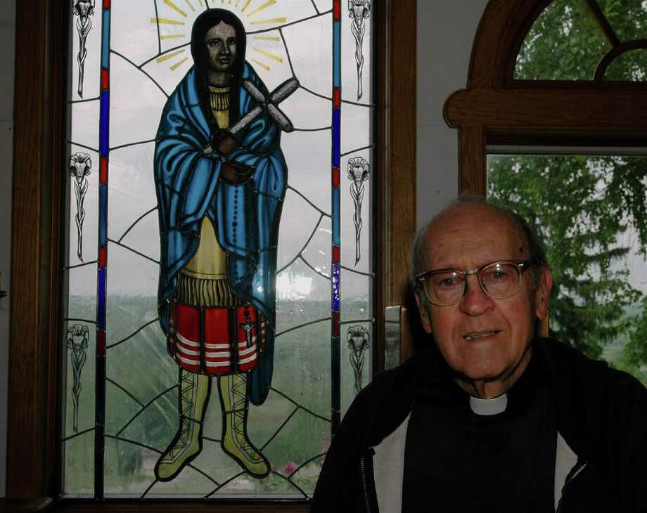The Rev. John Paret is shown at theShrine of Our Lady of Martyrs in Auriesville in this 2004 archive photo. Blessed Kateri Tekakwitha, the Lady of the Mohawks, shown in the stained glass window, was among seven  new saints approved Monday, Dec. 19, 2011, by Pope Benedict XVI. (Times Union archive) Photo: LUANNE M. FERRIS / ALBANY TIMES UNION