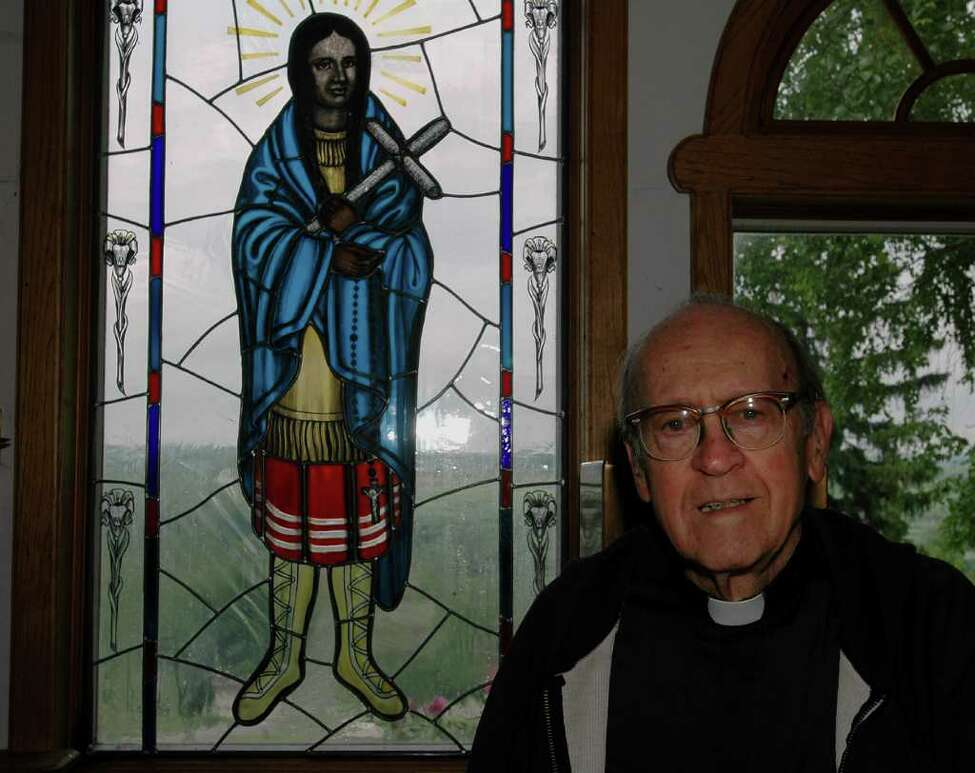 The Rev. John Paret is shown at theShrine of Our Lady of Martyrs in Auriesville in this 2004 archive photo. Blessed Kateri Tekakwitha, the Lady of the Mohawks, shown in the stained glass window, was among seven new saints approved Monday, Dec. 19, 2011, by Pope Benedict XVI. (Times Union archive)