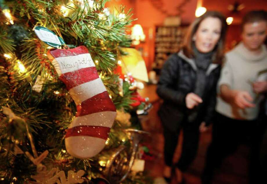 Republican presidential hopeful U.S. Rep. Michele Bachmann, R-Minn., second from right, walks past an ornament on a Christmas tree as she speaks to local residents during a campaign stop at the Merry Bees coffee shop, Monday, Dec. 19, 2011, in Hampton, Iowa. (AP Photo/Charlie Neibergall) Photo: Charlie Neibergall