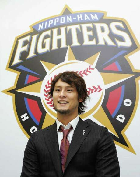 FILE - In this Jan. 6, 2011 file photo, Nippon Ham Fighters pitcher Yu Darvish smiles at a press conference in Sapporo, northern Japan, after a new contract signing that makes him the highest-paid player in Japanese professional baseball. Darvish ended months of speculation Thursday, Dec. 8, 2011 by saying he intends to make a move to Major League Baseball. (AP Photo/Kyodo News, File) JAPAN OUT, MANDATORY CREDIT, NO LICENSING IN CHINA, FRANCE, HONG KONG, JAPAN AND SOUTH KOREA / Kyodo News