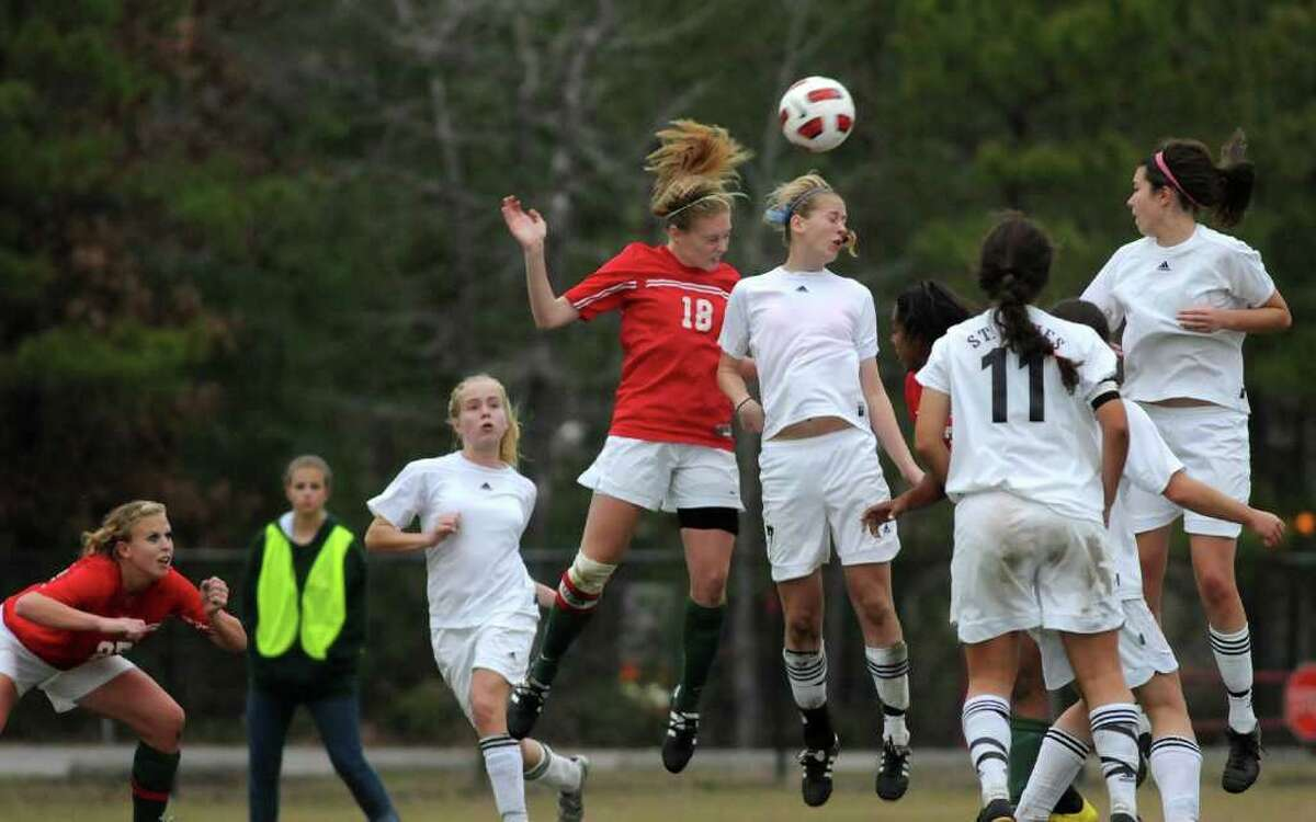The Woodlands senior defender Natalie Kintigh (#18) battles St. Agnes junior defender Caroline Taylor during their match at the 2011 Lady Highlander Invitational. Photo by Jerry Baker