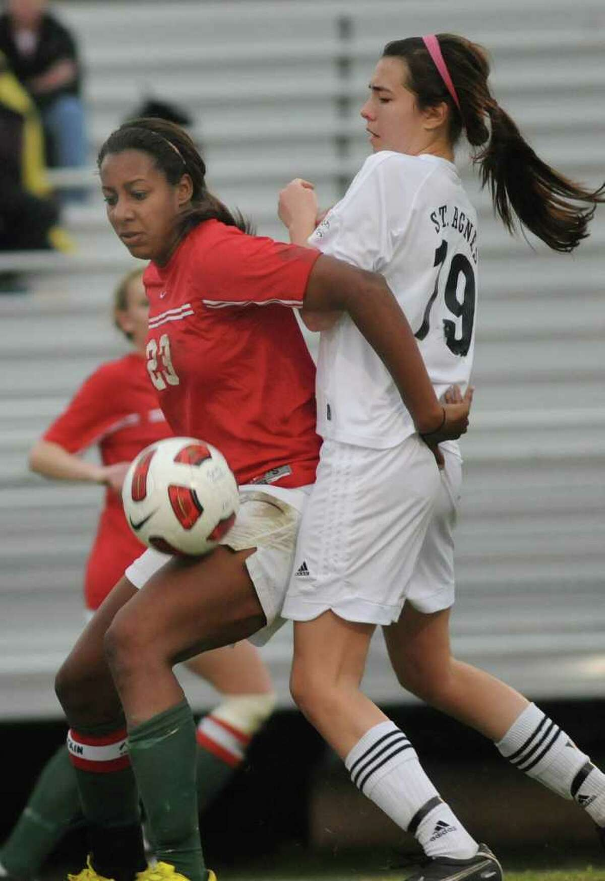 The Woodlands junior forward Lexi Ricketts, left, works against St. Agnes junior defender Caroline Casey during their match at the 2011 Lady Highlander Invitational. Photo by Jerry Baker