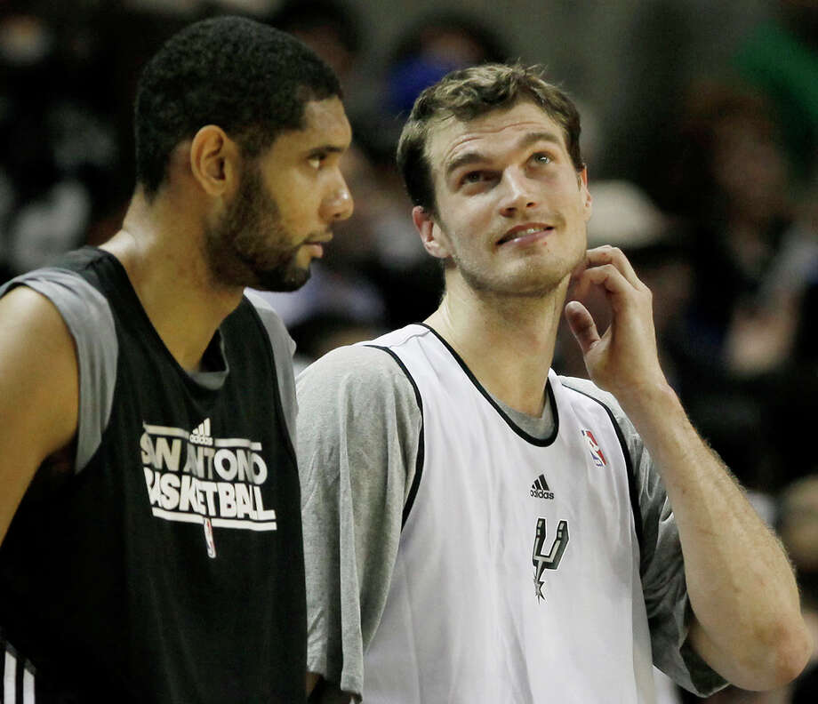 Spurs players Tim Duncan (left), playing for Black, and Tiago Splitter, playing for Silver, talk on the court during a scrimmage Monday, Dec. 19, 2011 at the AT&T Center. The Silver team, comprised of Spurs backups, beat the Black team of starters 83-75. Photo: Darren Abate, For The Express-News