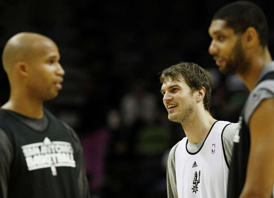 The Spurs' Tiago Splitter (center) jokes with teammates Richard Jefferson (left) and Tim Duncan during an intrasquad scrimmage on Monday, Dec. 19, 2011 at the AT&T Center. The Silver team, comprised of Spurs backups, beat the Black team of starters 83-75. Photo: Darren Abate, For The Express-News