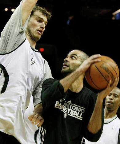 Spurs guard Tony Parker (right) is blocked by Spurs center Tiago Splitter during the team's Silver and Black intrasquad scrimmage on Monday, Dec. 19, 2011 at the AT&T Center. The Silver team, comprised of Spurs backups, beat the Black team of starters 83-75. Photo: Darren Abate, For The Express-News