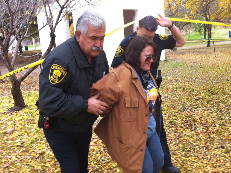 San Antonio Park Police took Sharon Young into custody shortly before noon Monday near a blocked-off adobe building at the park. Photo: Jessica Kwong/Express-News