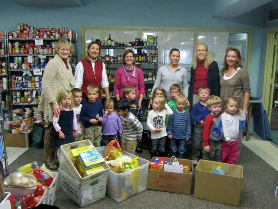 Sally Farrell, director of SMNS, and Wendy Hilboldt, coordinator of New Canaan Food Pantry (top, left) stand with SMNS 3s students and teachers and their donations. Photo: Contributed Photo