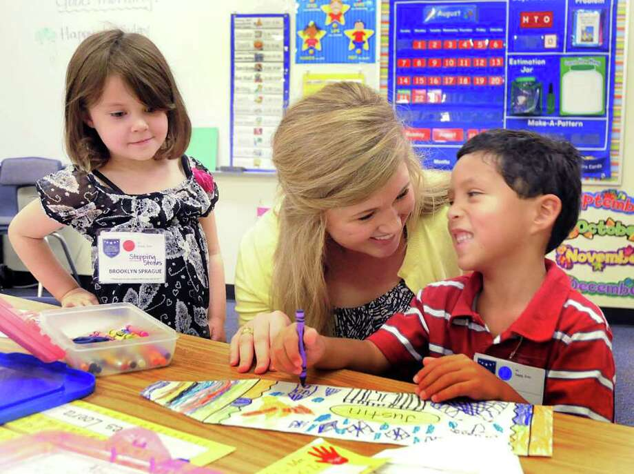DAVID HOPPER: FOR THE CHRONICLE MORE STUDENTS: Powell Elementary School first year teacher Abigail Ott worked with kindergarten students Brooklyn Sprague and James Loera during the first day of school. Classrooms across the state are more crowded this year. Photo: David Hopper / freelance
