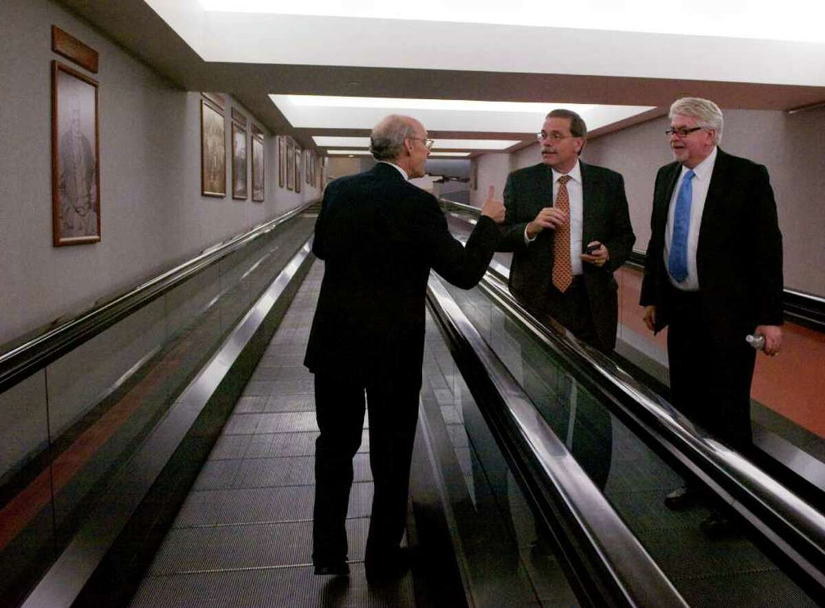 Gov. Dan Malloy's Chief of Staff Tim Bannon, left, with Jackson Laboratory's Vice President for Advancement and External Relations Mike Hyde, center, and Deputy Commissioner of the Connecticut Department of Economic and Community Development Kip Bergstrom as they pass each other on the moving walkway at the state Capitol in Hartford, Conn., October 26, 2011. A package of state assistance for the lab - worth almost $300m - was approved on a party-line vote of the legislature that evening.
