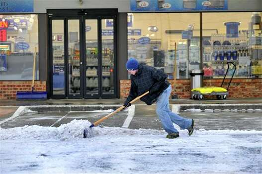 Kevin Wesson shovels a path for customers at the Water Still, on Tuesday morning Dec. 20, 2011 after an overnight storm covered Amarillo with about an inch of ice and snow. Several major thoroughfares were closed after the storm clipped the far northwest part of the state the day before the official start of winter.  (AP Photo/Amarillo Globe-News, Michael Schumacher)    MANDATORY CREDIT; MAGS OUT; TV OUT; INTERNET OUT; AP MEMBERS ONLY Photo: Associated Press