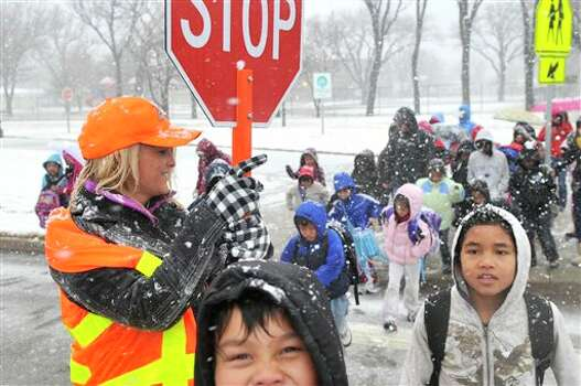 """In a Monday Dec. 19, 2011 photo, Jaydon Deavers, holding stop sign, help kids cross Plains Boulevard  in Amarillo, Texas as the """"After School Rocks"""" program left Margaret Wills Elementary School. A severe winter storm hit Amarillo Monday dropping about an inch of snow and ice and closing several highways in the Texas Panhandle. Travelers in the Texas Panhandle were urged to stay off ice-packed roads Tuesday after up to 10 inches of snow covered parts of the region. Several major thoroughfares were closed after the storm clipped the far northwest part of the state the day before the official start of winter.  (AP Photo/Amarillo Globe-News, Michael Schumacher) Photo: Associated Press"""