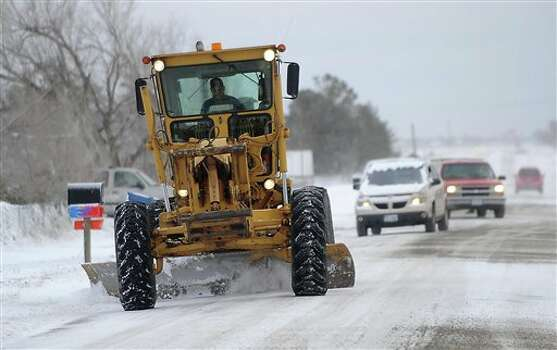 A Potter County road grader works to clear parts of Indian Hills Road Tuesday, Dec. 20, 2011 in Amarillo, Texas. Travelers in the Texas Panhandle were urged to stay off ice-packed roads Tuesday after up to 10 inches of snow covered parts of the region. Several major thoroughfares were closed after the storm clipped the far northwest part of the state the day before the official start of winter. (AP Photo/The Amarillo Globe-News, Michael Norris) Photo: Associated Press