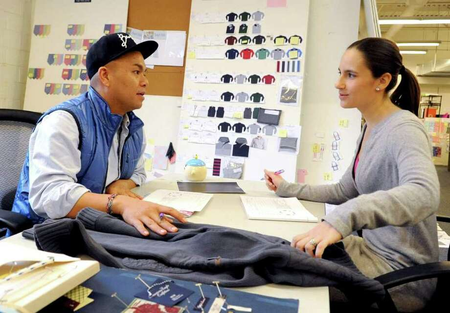 Daniel Armosilla, left, and Tori McBrien, right, talk about a sweater design at Vineyard Vines in Stamford on Tuesday, December 20, 2011. Photo: Lindsay Niegelberg / Stamford Advocate