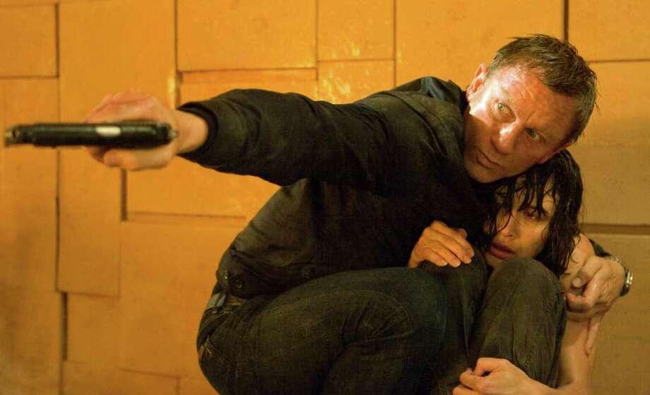 "James Bond (Daniel Craig) shields Camille (Olga Kurylenko) in ""Quantum of Solace."" Photo: KAREN BALLARD, EON PRODUCTIONS / Quantum of Solace © 2008 Danjaq, LLC, United Artists Corporation, Columbia Pictures Industries, Inc. All Rights Reserved."