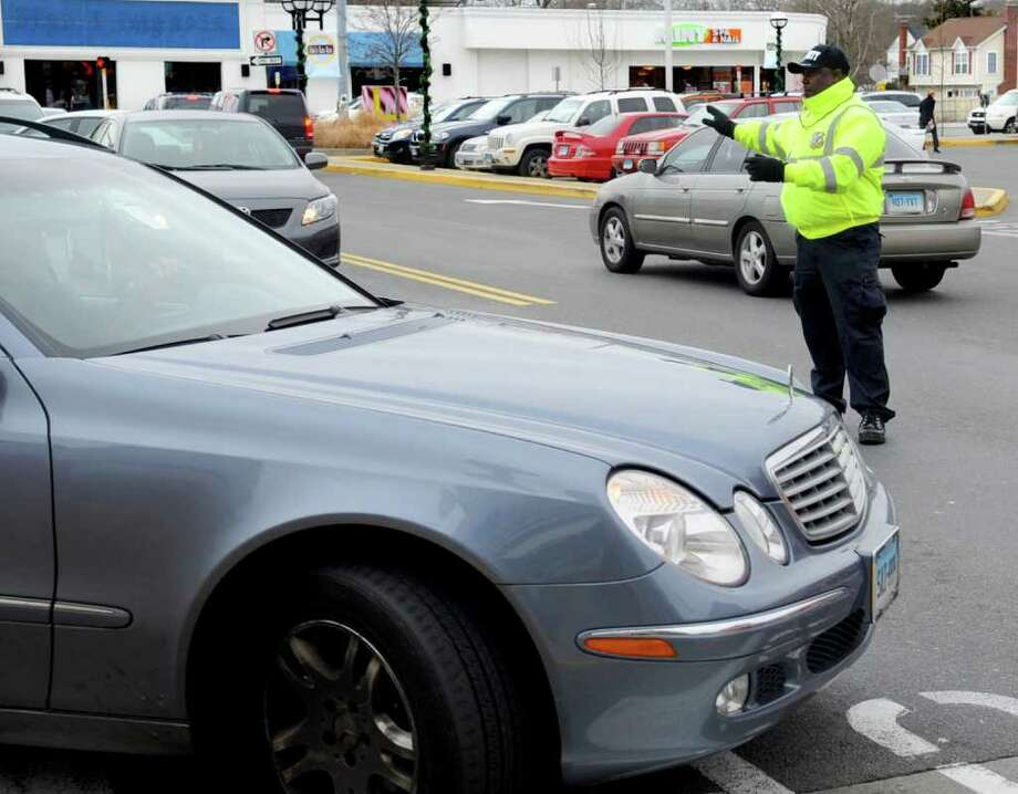 Everol Campbell of Integrated Security directs traffic at the Ridgeway Shopping Center in Stamford on Tuesday, December 20, 2011. Photo: Lindsay Niegelberg / Stamford Advocate