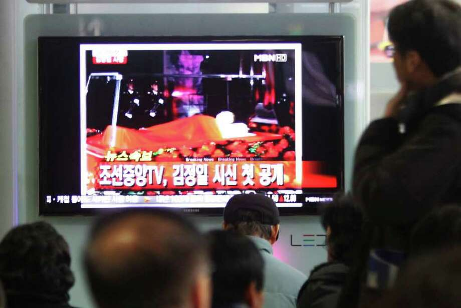 """People watch a TV screen showing the body of late North Korean leader Kim Jong Il, at Seoul Railway Station in Seoul, South Korea, Tuesday, Dec. 20, 2011. The letters on the screen read"""" Korean Central TV opens  Kim Jong-Il's body"""". AP Photo/Ahn Young-joon) Photo: Ahn Young-joon / AP"""