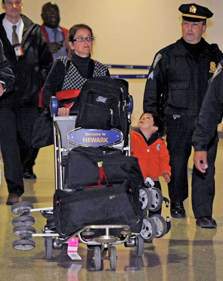 Lori Berenson arrives from Lima, Peru, with her son Salvador Apari at Newark Liberty International Airport, Tuesday, Dec. 20, 2011 in Newark, N.J. Berenson, who was convicted of aiding Peruvian guerrillas and served 15 years before she was paroled last year, said she fully intended to return to Peru by the court-ordered deadline of Jan. 11. (AP Photo/Henny Ray Abrams) Photo: Henny Ray Abrams / FR151332 AP