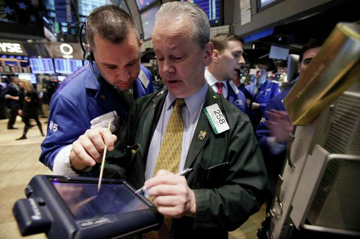 Traders James Lodewick, left, and James Riley, center, on the floor of the New York Stock Exchange Tuesday, Dec. 20, 2011. Stocks are surging after the opening bell following encouraging signs out of Europe and a jump in apartment building in the U.S.