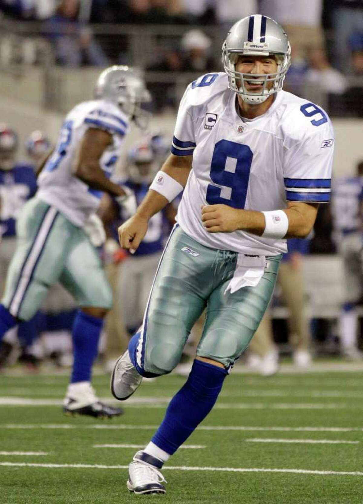 Dallas Cowboys quarterback Tony Romo heads to the sideline after passing the ball to John Phillips for a touchdown against the New York Giants during the first half of an NFL football game Sunday, Dec. 11, 2011, in Arlington, Texas.