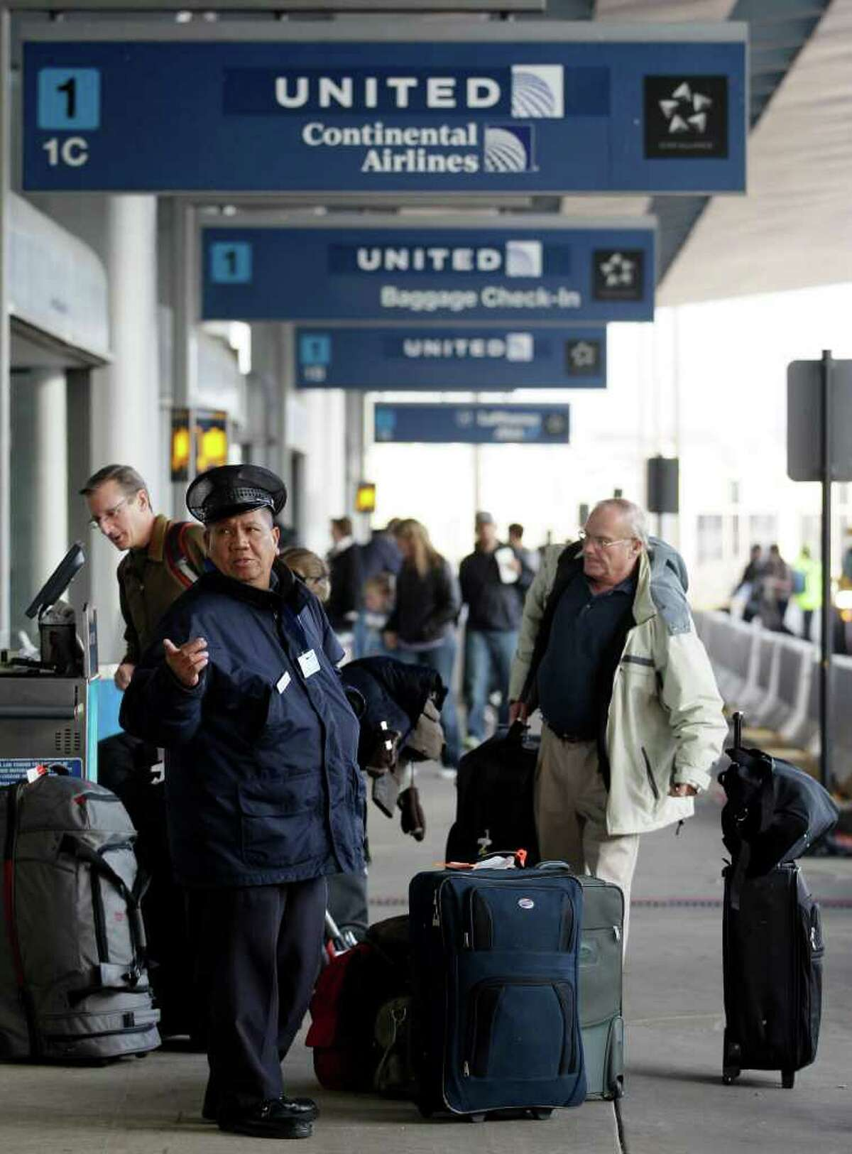 Travelers check their luggage bags with employees at United Airline before ticketing at O'Hare International Airport in Chicago on Wednesday, Nov. 23, 2011. Thursday marks the Thanksgiving holiday, one of the busiest travel days of the year.