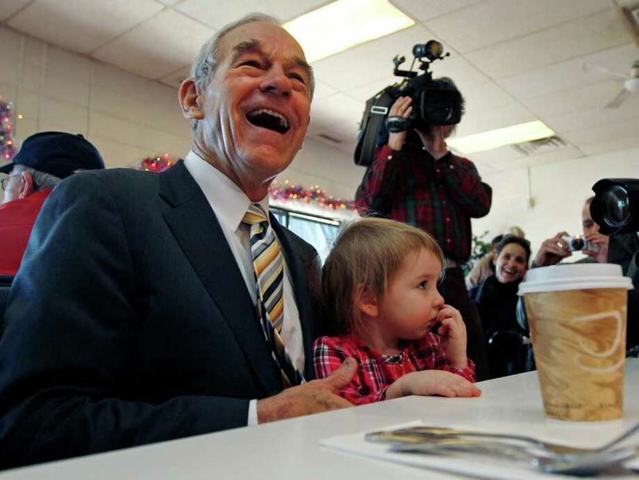 Republican presidential candidate Rep. Ron Paul, R-Texas, laughs as he sits down with Elizabeth Rose Chamberlain, 3, of Epping, N.H., while campaigning at the Early Bird Cafe in Plaistow, N.H., Tuesday Dec. 20, 2011. Photo: AP