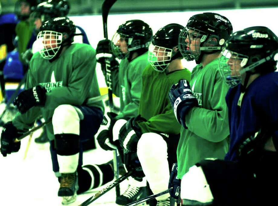 SPECTRUM/Green Wave skaters listen to words of guidance from their coaches as they prep for the New Milford High School ice hockey season. December 2011 Photo: Norm Cummings