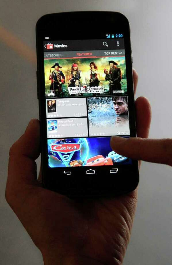 An Associated Press reporter demonstrates the Samsung Galaxy Nexus phone, which runs the newest version of Google's Android mobile software, Ice Cream Sandwich, during a product review in San Francisco, Tuesday, Dec. 13, 2011. Photo: AP