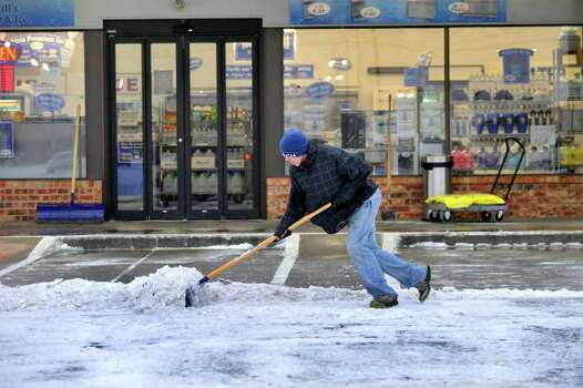 Kevin Wesson shovels a path for customers at the Water Still, on Tuesday morning Dec. 20, 2011 after an overnight storm covered Amarillo with about an inch of ice and snow. Several major thoroughfares were closed after the storm clipped the far northwest part of the state the day before the official start of winter.  (AP Photo/Amarillo Globe-News, Michael Schumacher)    MANDATORY CREDIT; MAGS OUT; TV OUT; INTERNET OUT; AP MEMBERS ONLY Photo: AP