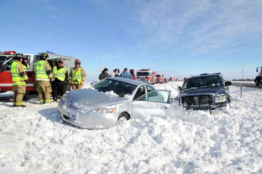 Emergency responders assists victims of a multiple-vehicle accident on westbound  Interstate 40 about 15 miles west of Amarillo, Texas Tuesday, Dec. 20, 2011. Travelers in the Texas Panhandle were urged to stay off ice-packed roads Tuesday after up to 10 inches of snow covered parts of the region. Photo: AP