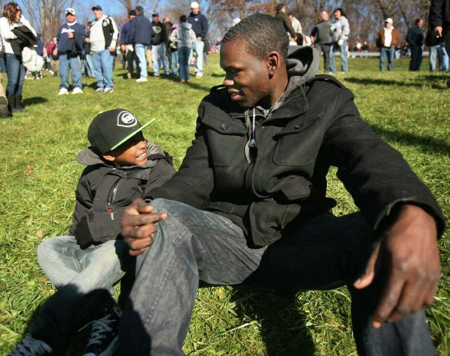 Nigel Ingram, member of the state championship 2002 and 2003 Ansonia Chargers football teams, watches the 2011 Thanksgiving Day game between Ansonia and Naugatuck, at Naugatuck High School, with his nephew, Machi, 5. Photo: Brian A. Pounds / Connecticut Post