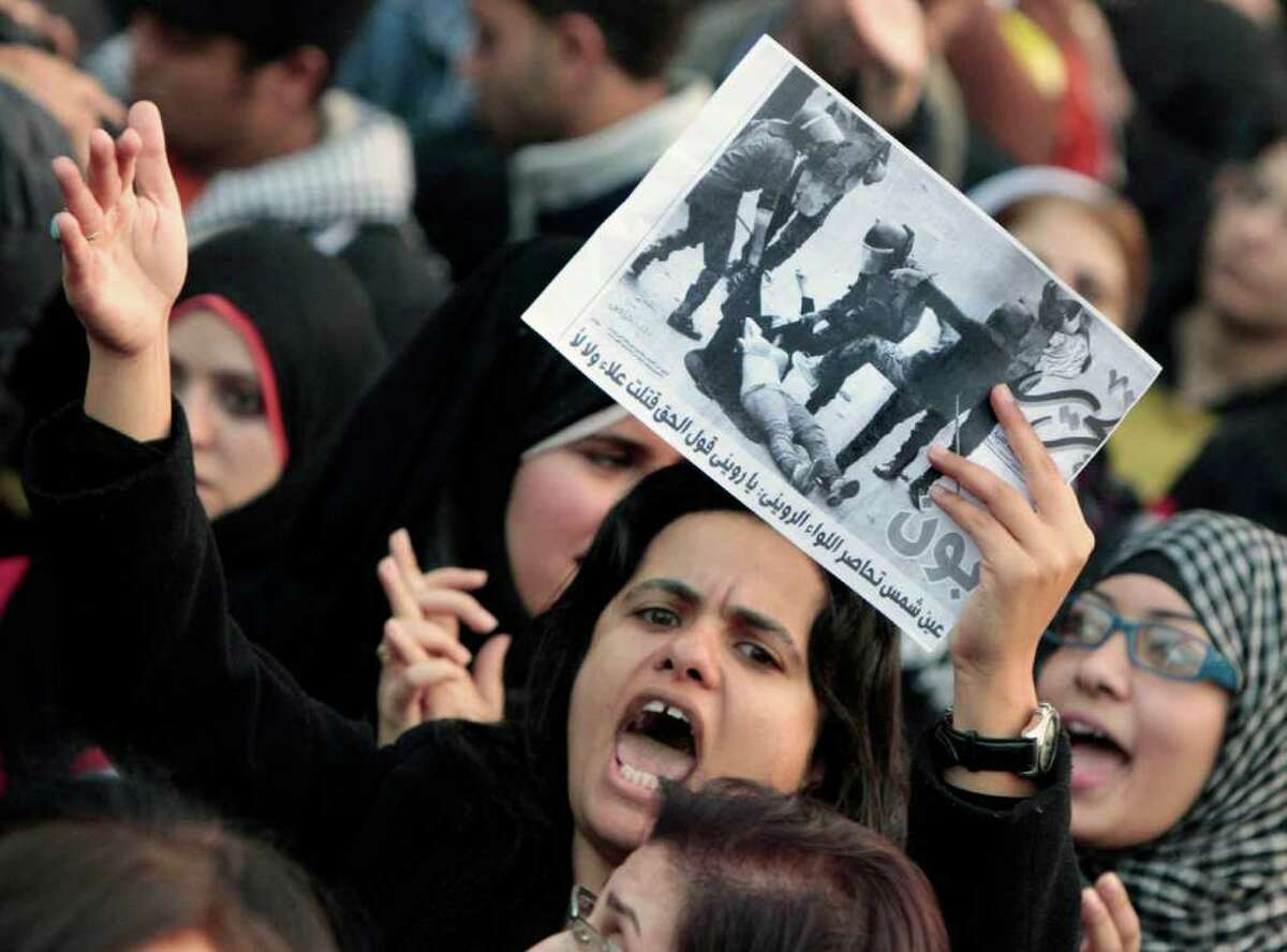 An Egyptian woman raises a copy of Al Tahrir newspaper fronted by a picture showing half naked woman protester beaten by army soldiers as hundreds of Egyptian women march at Cairo streets angered by the recent violence used against them during clashes between police and protesters in Cairo, Egypt Tuesday, Dec. 20, 2011. Egypt's ruling generals are coming under mounting criticism at home and abroad for the military's use of excessive force against unarmed protesters, including women, as they try to crush the pro-democracy movement calling for their ouster. Arabic read