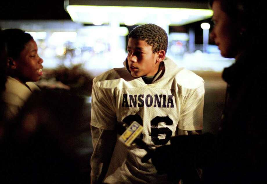 Michael Ayala (center) listens to his teammate Rafine Buggs talk to reporters outside Riverside Apartments in Ansonia, Conn. Nov. 27th, 2002 following the shooting death of fellow Ansonia High School football player Damontis Johnson. Photo: File Photo / Connecticut Post File Photo