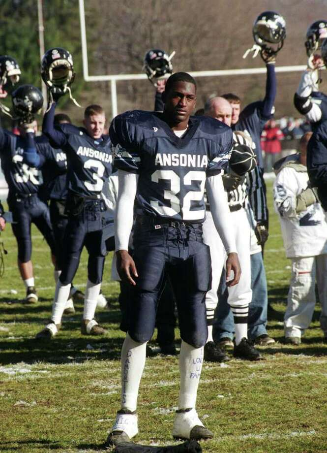 Ansonia High School quarterback Kenney Tinney, wearing the No. 32 jersey of his cousin and fellow Ansonia football player Damontis Johnson, stands at attention during the National Anthem before the start of his team's annual Thanksgiving day game against Naugatuck in Ansonia, Conn. Nov. 28th, 2002. Johnson was fatally shot the day before the game. Tinney wore his slain cousin's jersey for the game, which Ansonia won 43-9. (Connecticut Post Photo / Brian A. Pounds) Photo: Brian A. Pounds / Connecticut Post