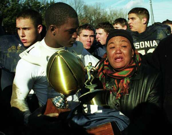 Mia Johnson, right, mother of slain Ansonia football player Damontis Johnson, is comforted by her nephew Kenney Tinney, quarterback of the team, after being presented the game ball and trophy in honor of her son following the annual Thanksgiving day game against Naugatuck, Nov. 28th, 2002. Damontis Johnson was killed the day before the game, and Tinney wore his cousins jersey #32 during the game. Photo: Brian A. Pounds / Connecticut Post