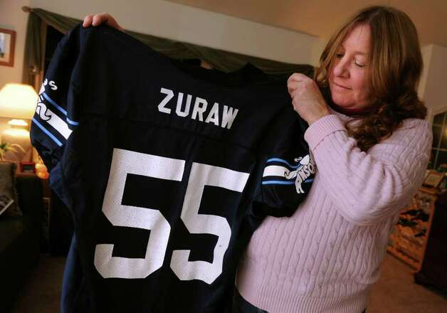 Cathy Zuraw holds up her son's Ansonia High School football jersey at her home in Ansonia, Conn.  Her son, Steve Zuraw, played from 2002-2003, when they won back-to-back state titles.  Steve died in a car accident in June 2009, a month after he graduated from college. Photo: Autumn Driscoll / Connecticut Post